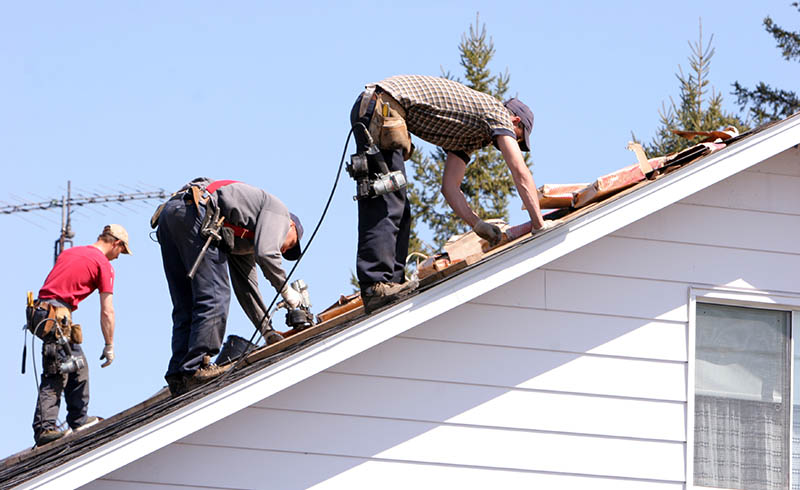 Three roofers working on a roof restoration project